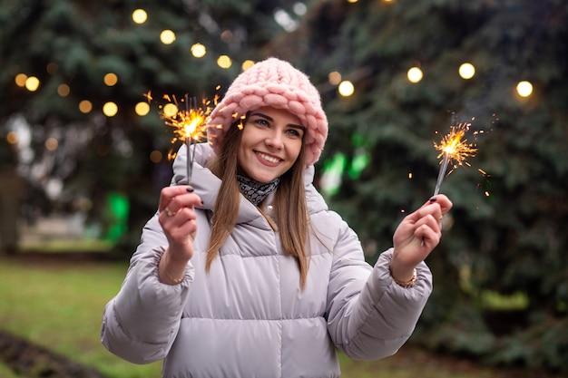 Une jeune femme joyeuse porte un chapeau et un manteau tricotés roses s'amusant avec des cierges magiques dans la rue près de l'arbre de noël