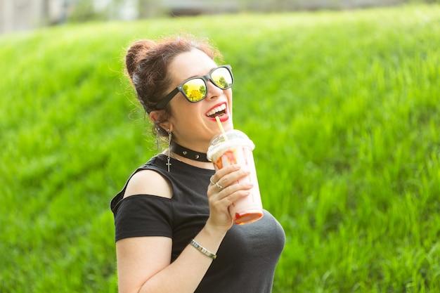 Jeune femme joyeuse positive dans des vêtements punk élégants et des lunettes tenant un milkshake dans ses mains lors d'une promenade dans le parc par une chaude soirée d'été. le concept de détente et de plaisir en ville.