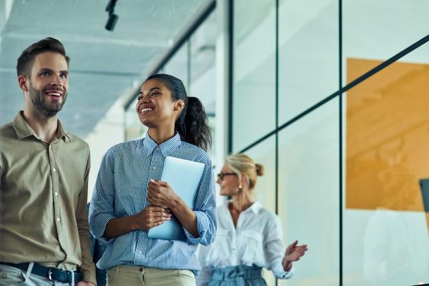 Jeune femme joyeuse de race mixte tenant un ordinateur portable et parlant avec son collègue masculin en position debout