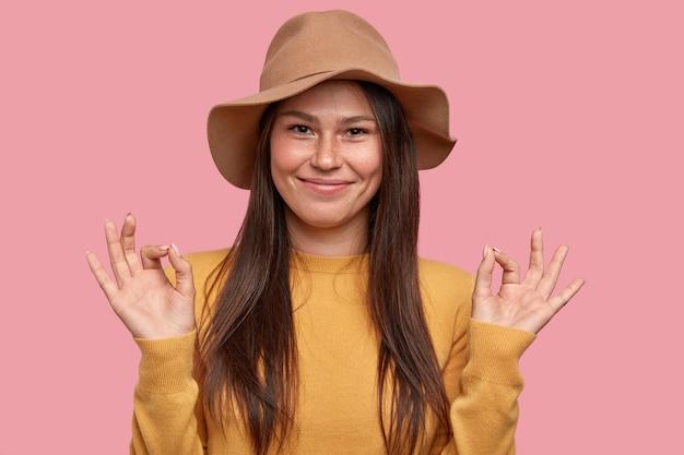 Une jeune femme joyeuse satisfaite accepte d'aider, de montrer un geste fin, vêtue de vêtements à la mode