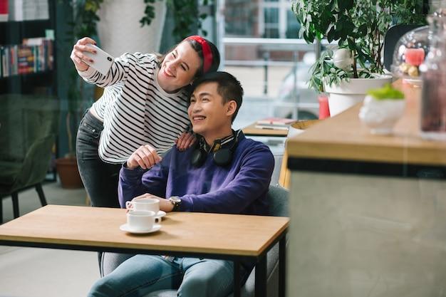 Jeune femme joyeuse souriante et prenant des photos avec son petit ami tout en se tenant à côté de lui