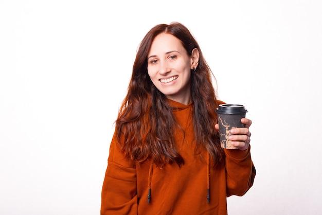 Jeune femme joyeuse sourit à la caméra et tient une tasse avec une boisson chaude en elle