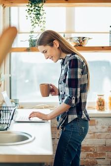 Jeune femme joyeuse tenant une tasse et utilisant son ordinateur portable moderne à la maison