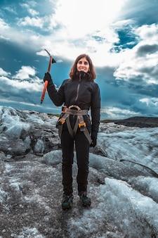 Une jeune femme joyeuse sur le trekking sur glace du glacier svinafellsjokull. islande