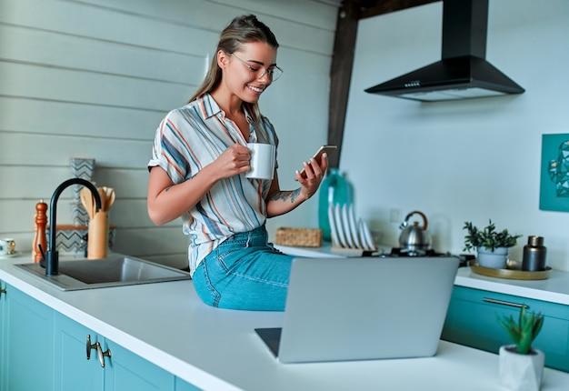 Une jeune femme joyeuse vêtue de vêtements décontractés et de lunettes est assise sur un plan de travail avec une tasse de café et un téléphone tout en travaillant sur un ordinateur portable à la maison dans sa cuisine. travail indépendant à domicile.