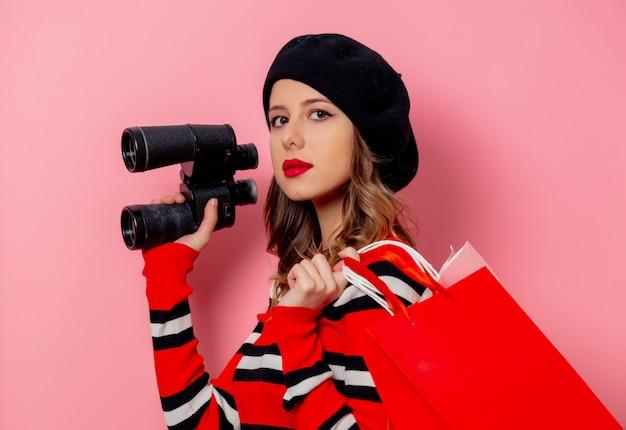 Jeune femme avec des jumelles et des sacs à provisions sur mur rose