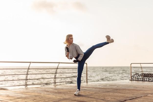 Jeune femme kickboxer en vêtements de sport avec les mains enveloppées dans des trains de bandages coup de pied sur la plage au lever du soleil