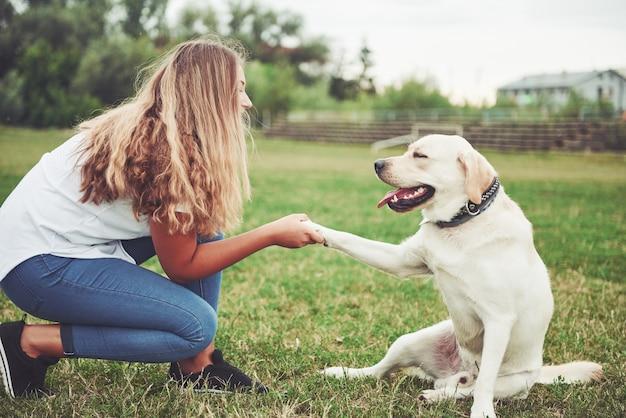 Jeune femme avec labrador à l'extérieur. femme sur une herbe verte avec chien labrador retriever.