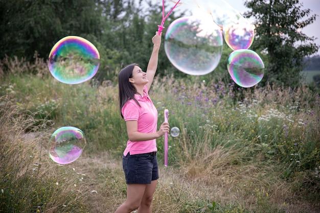 Une jeune femme lance de grandes bulles de savon colorées parmi l'herbe dans la nature.