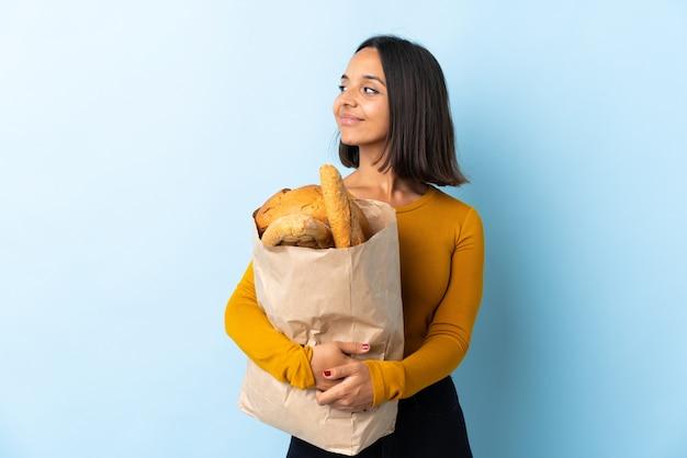 Jeune femme latine l'achat de pains isolés sur bleu à la recherche sur le côté