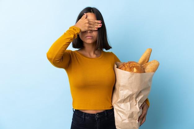 Jeune femme latine achetant des pains isolés sur les yeux bleus coning par les mains. je ne veux pas voir quelque chose