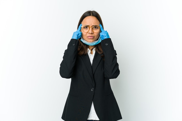 Jeune femme latine d'affaires portant un masque pour se protéger de covid isolé sur un mur blanc axé sur une tâche, en gardant l'index pointant la tête
