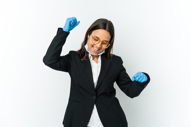Jeune femme latine d'affaires portant un masque pour se protéger de covid isolé sur un mur blanc célébrant une journée spéciale, saute et lever les bras avec énergie