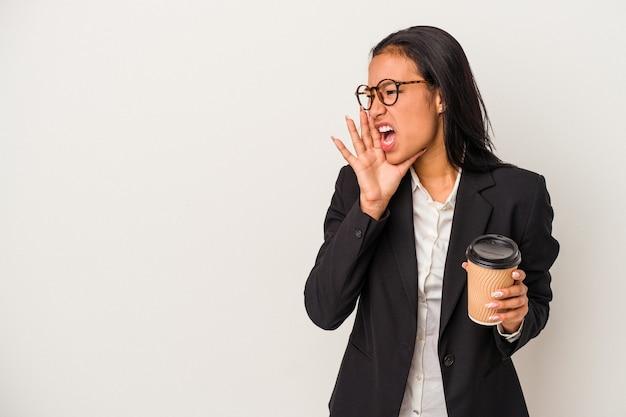 Jeune femme latine d'affaires tenant un café à emporter isolé sur fond blanc criant et tenant la paume près de la bouche ouverte.