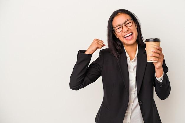 Jeune femme latine d'affaires tenant un café à emporter isolé sur fond blanc levant le poing après une victoire, concept gagnant.