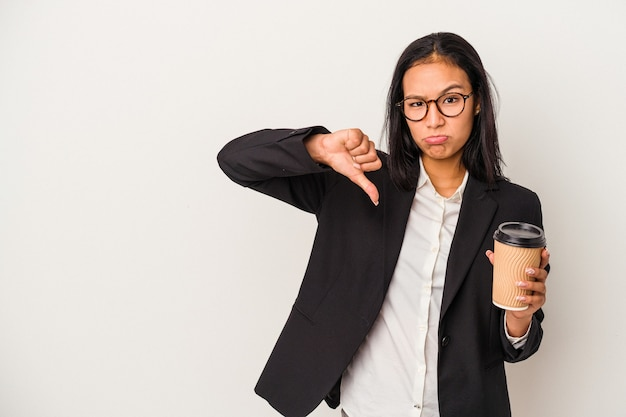Jeune femme latine d'affaires tenant un café à emporter isolé sur fond blanc montrant un geste d'aversion, les pouces vers le bas. notion de désaccord.
