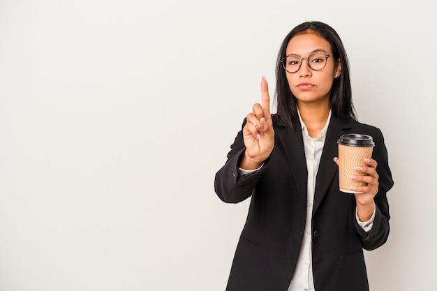 Jeune femme latine d'affaires tenant un café à emporter isolé sur fond blanc montrant le numéro un avec le doigt.