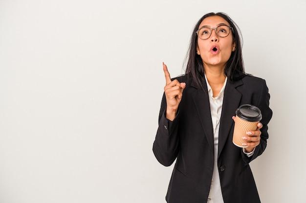 Jeune femme latine d'affaires tenant un café à emporter isolé sur fond blanc pointant vers le haut avec la bouche ouverte.