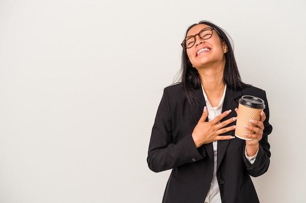 Jeune femme latine d'affaires tenant un café à emporter isolé sur fond blanc rit fort en gardant la main sur la poitrine.