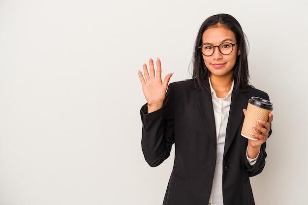Jeune femme latine d'affaires tenant un café à emporter isolé sur fond blanc souriant joyeux montrant le numéro cinq avec les doigts.
