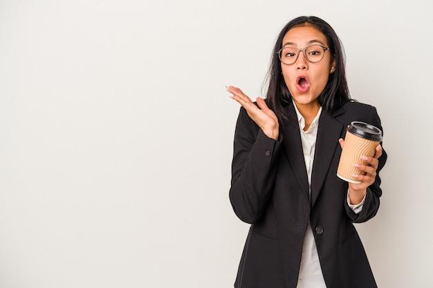 Jeune femme latine d'affaires tenant un café à emporter isolé sur fond blanc surpris et choqué.