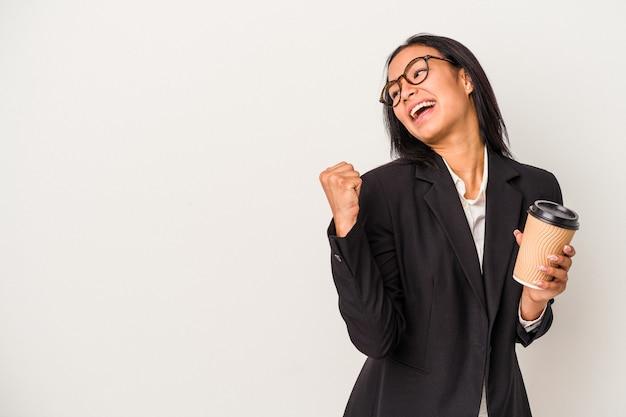 Jeune femme latine d'affaires tenant un café à emporter isolé sur des points de fond blanc avec le pouce loin, riant et insouciant.