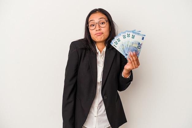 Jeune femme latine d'affaires tenant des factures de café isolé sur fond blanc hausse les épaules et ouvre les yeux confus.