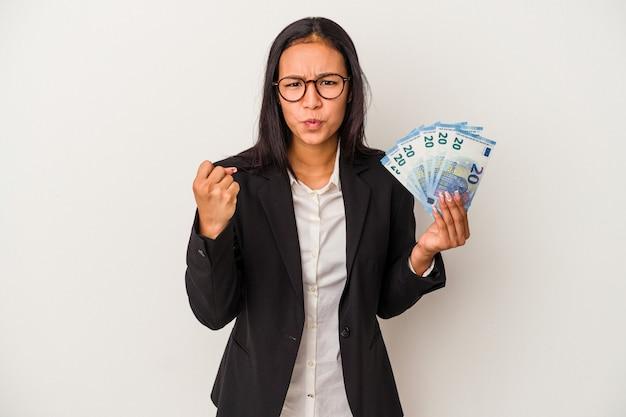 Jeune femme latine d'affaires tenant des factures de café isolé sur fond blanc montrant le poing à la caméra, expression faciale agressive.