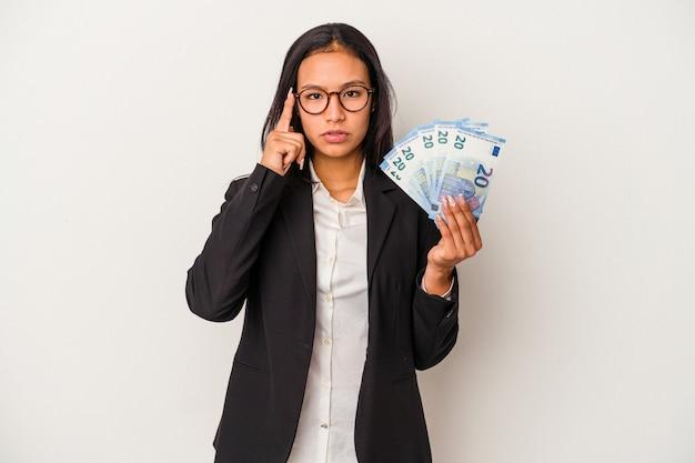 Jeune femme latine d'affaires tenant des factures de café isolées sur fond blanc pointant le temple avec le doigt, pensant, concentrée sur une tâche.