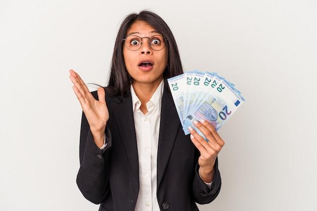 Jeune femme latine d'affaires tenant des factures isolées sur fond blanc surpris et choqué.