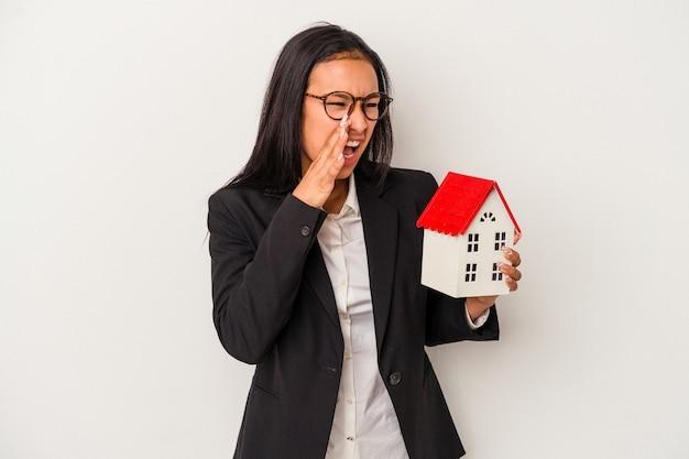 Jeune femme latine d'affaires tenant une maison de jouet isolée sur fond blanc criant et tenant la paume près de la bouche ouverte.