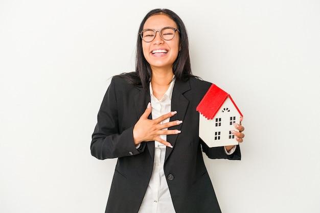 Jeune femme latine d'affaires tenant une maison de jouet isolée sur fond blanc éclate de rire en gardant la main sur la poitrine.