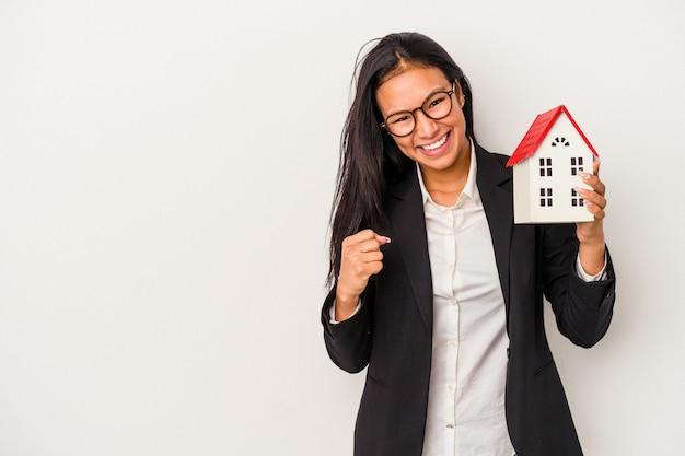 Jeune femme latine d'affaires tenant une maison de jouet isolée sur fond blanc levant le poing après une victoire, concept gagnant.