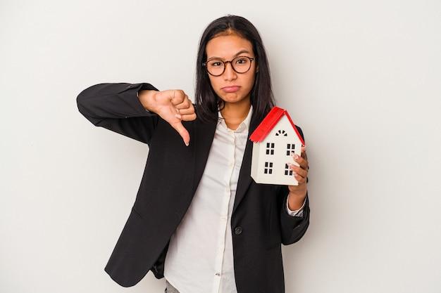 Jeune femme latine d'affaires tenant une maison de jouet isolée sur fond blanc montrant un geste d'aversion, les pouces vers le bas. notion de désaccord.