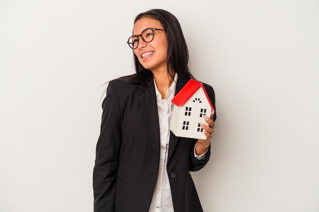 Jeune femme latine d'affaires tenant une maison de jouet isolée sur fond blanc regarde de côté souriante, gaie et agréable.