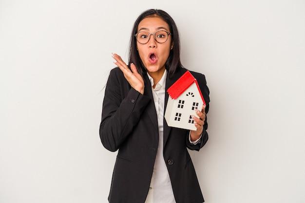 Jeune femme latine d'affaires tenant une maison de jouet isolée sur fond blanc surpris et choqué.