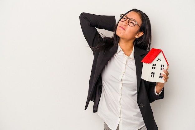 Jeune femme latine d'affaires tenant une maison de jouet isolée sur fond blanc touchant l'arrière de la tête, pensant et faisant un choix.