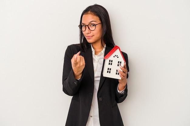 Jeune femme latine d'affaires tenant une maison de jouets isolée sur fond blanc pointant du doigt vers vous comme si vous vous invitiez à vous rapprocher.