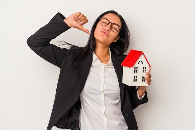 Jeune femme latine d'affaires tenant une maison de jouets isolée sur fond blanc se sent fière et confiante, exemple à suivre.