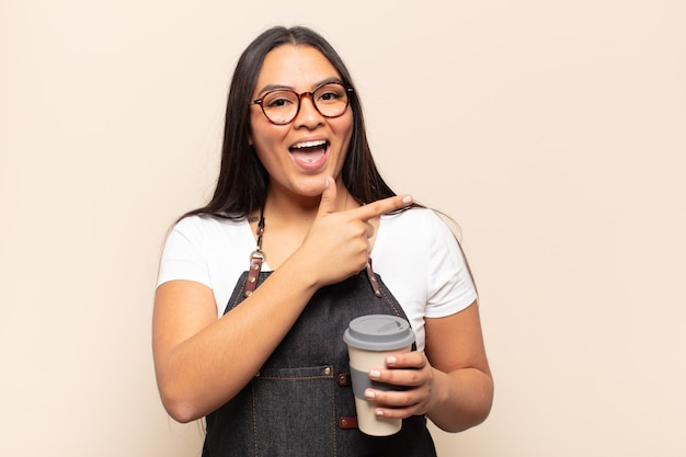 Jeune femme latine à l'air excitée et surprise pointant vers le côté et vers le haut pour copier l'espace