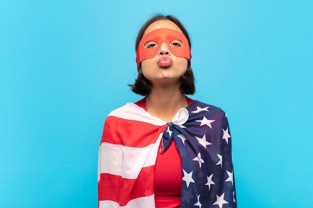 Jeune femme latine en appuyant sur les lèvres avec une expression mignonne, amusante, heureuse et charmante, envoyant un baiser