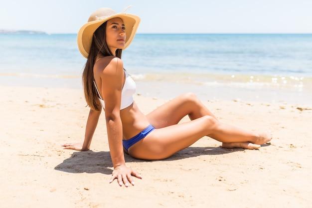 Jeune femme latine au chapeau de paille assis sur la plage de la mer