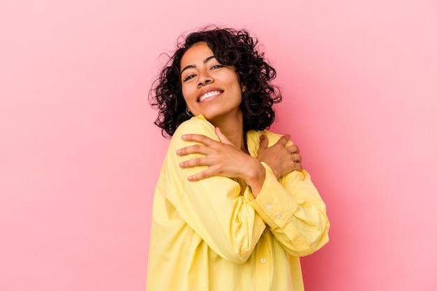 Jeune femme latine bouclée isolée sur fond rose câlins, souriant insouciant et heureux.