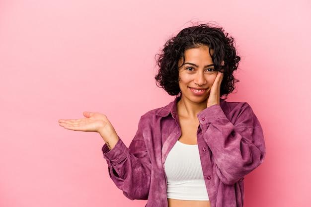 Jeune femme latine bouclée isolée sur fond rose détient un espace de copie sur une paume, gardez la main sur la joue. émerveillé et ravi.