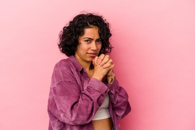 Jeune femme latine bouclée isolée sur fond rose effrayée et effrayée.