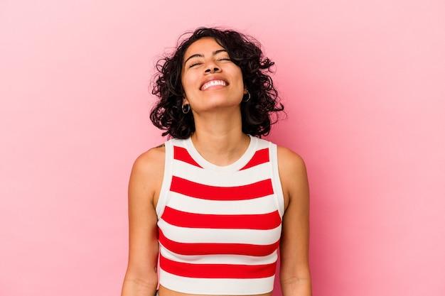 Jeune femme latine bouclée isolée sur fond rose rit et ferme les yeux, se sent détendue et heureuse.