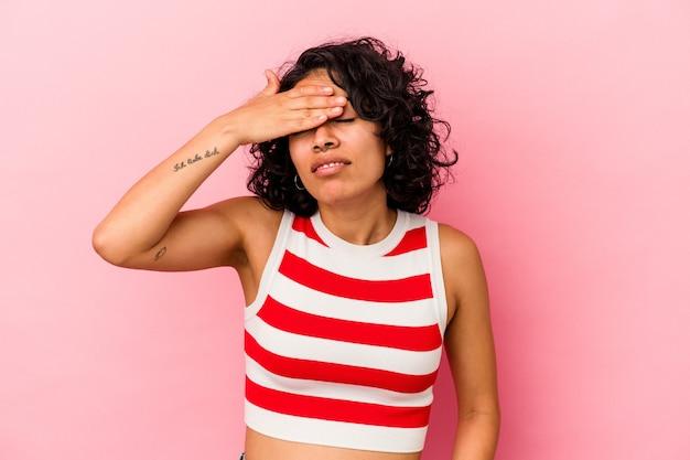 Jeune femme latine bouclée isolée sur fond rose touchant les tempes et ayant des maux de tête.