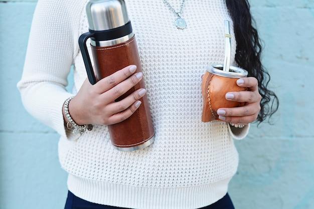 Jeune femme latine buvant du thé traditionnel yerba mate.
