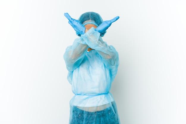 Jeune femme latine de chirurgien gardant deux bras croisés, concept de déni.
