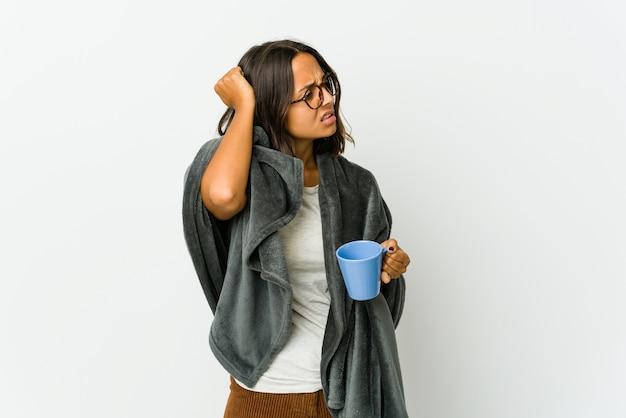 Jeune femme latine avec couverture isolée sur un mur blanc fatigué et très endormi en gardant la main sur la tête.
